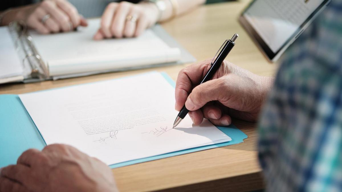 Hand signing papers in document.