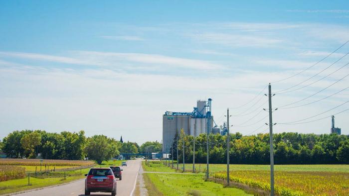 Cars driving through ag land into rural town.