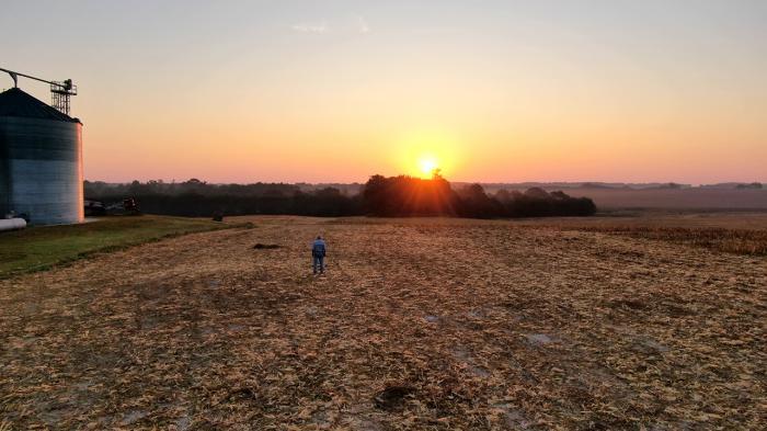 Grain bin in field at dusk.