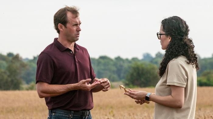 Man and woman talking in field.