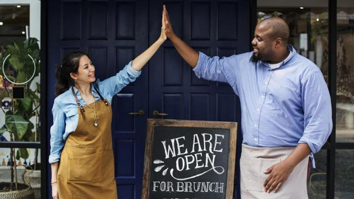 Couple with open sign in front of store.