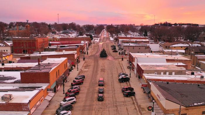 Drone shot looking down main street of small town.